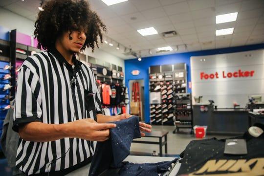 Lake View athlete JP Rodriguez folds clothes Thursday, Sept. 27, 2018, at Foot Locker.