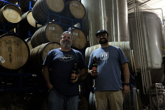 Dogfish Head brewmaster Mark Safarik and brewing supervisor Bill Marchi stand amid barrels of wild aged beers with KnottyBits, the brewery's newest funky ale, set for release Sept. 29.