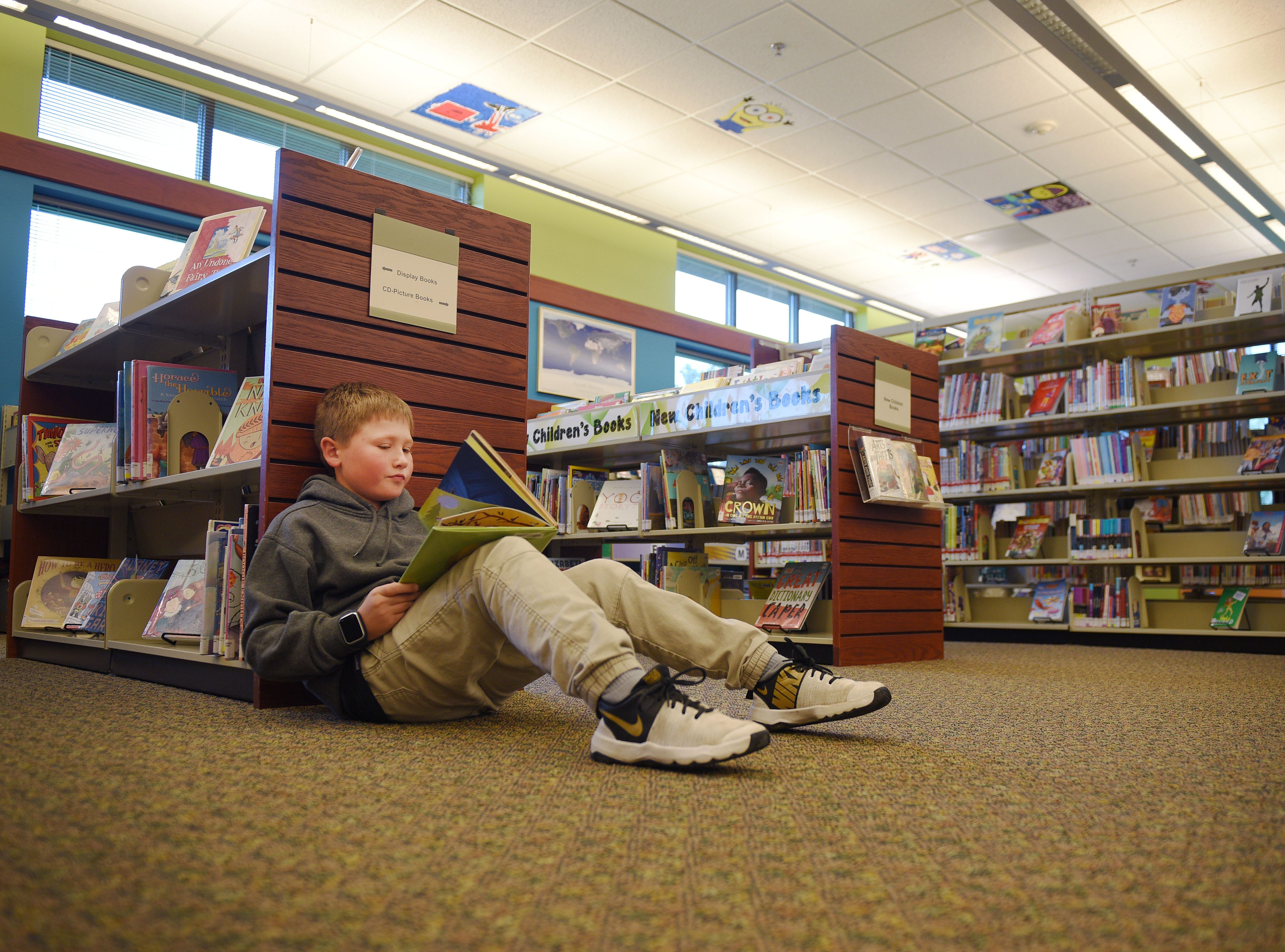 Charlie Heylens reads at the Oak View Library after school Wednesday, Sept 26, at the library in Sioux Falls.
