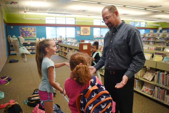 Oak View Library branch manager James Borchert talks to Savannah Reid and Grace Leiss after school Sept. 26, at the library in Sioux Falls. Borchert stands by the entrance of the library to greet kids with high-fives every day after school.