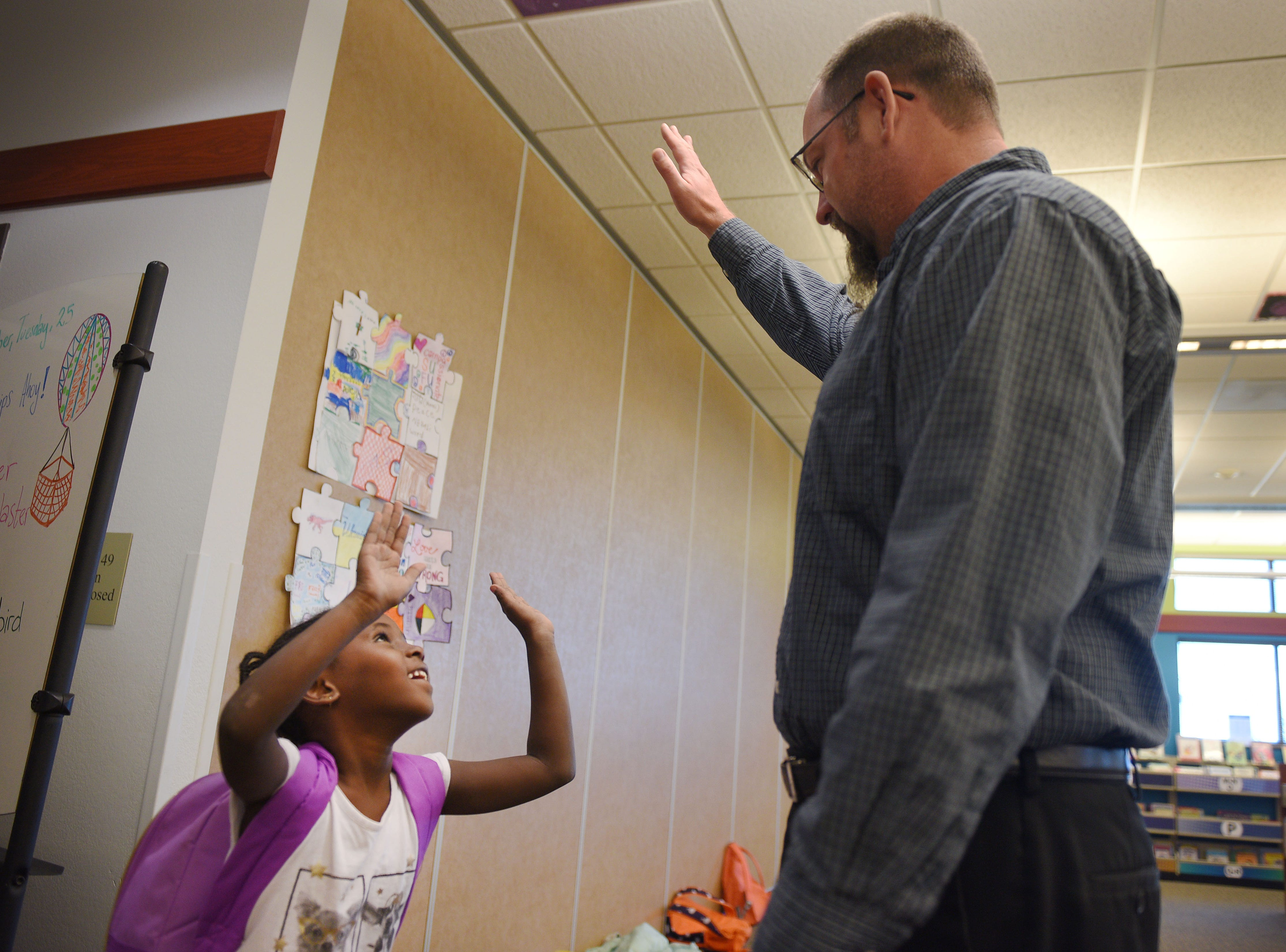 Oak View Branch Librarian James Borchert high fives Sara Akot-Kuel when she walks through the doors at the library after school Wednesday, Sept 26, at the library in Sioux Falls.