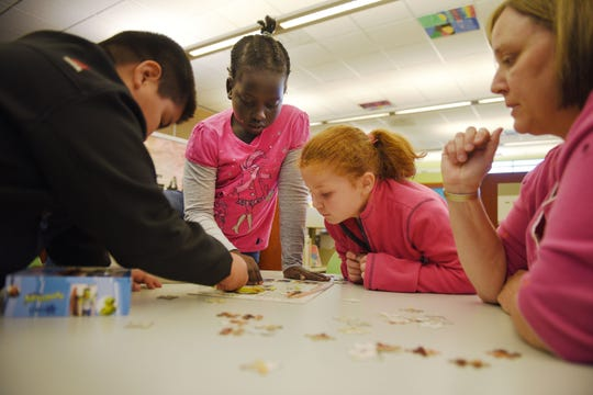 Sergio Diego, from left, Ayen Deng, Grace Leiss and library associate Stephanie Ode work on a puzzle after school at the Oak View Library Wednesday, Sept 26, at the library in Sioux Falls.