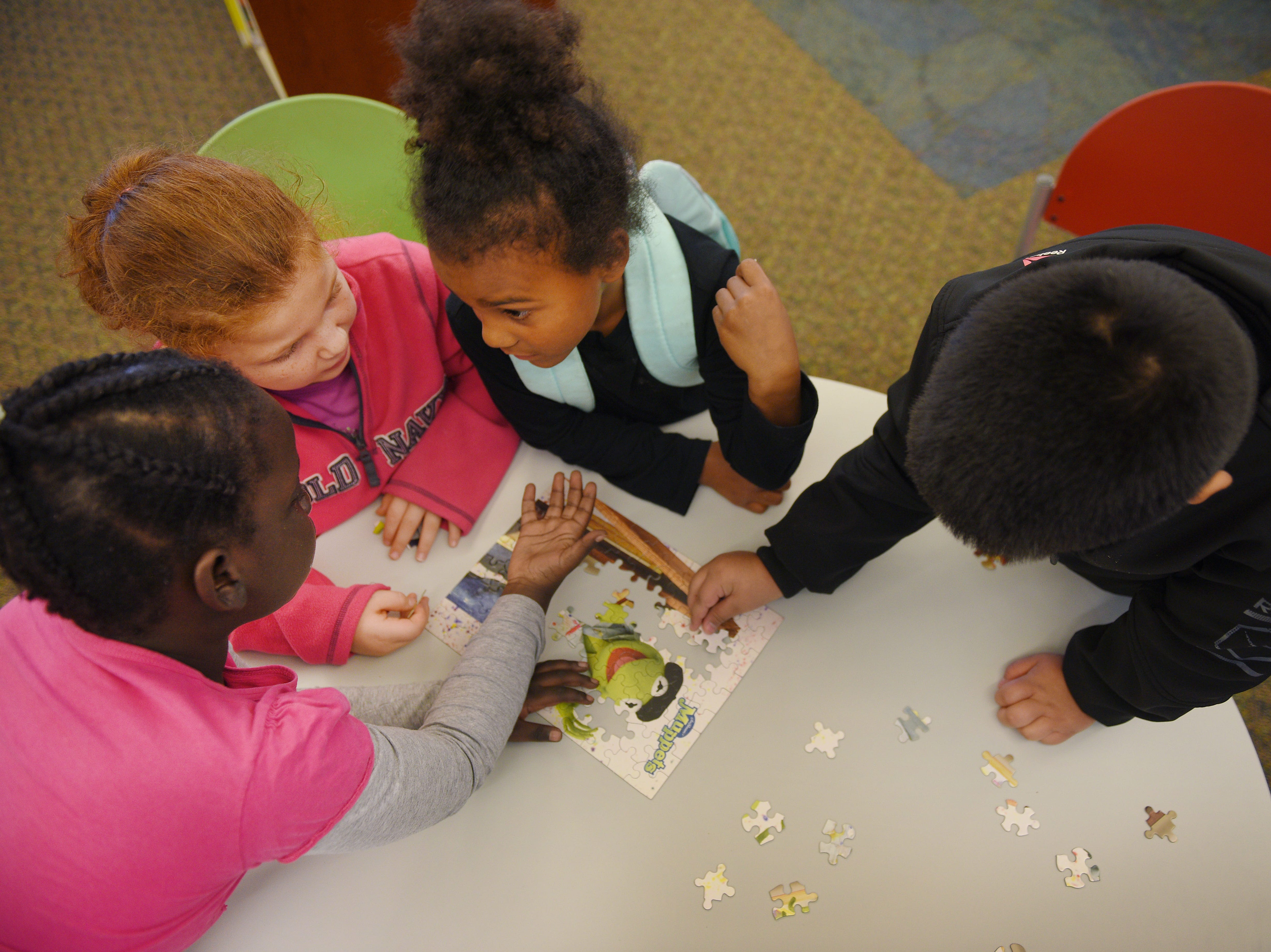 Kids work on a puzzle at the Oak View Library after school Wednesday, Sept 26, at the library in Sioux Falls.