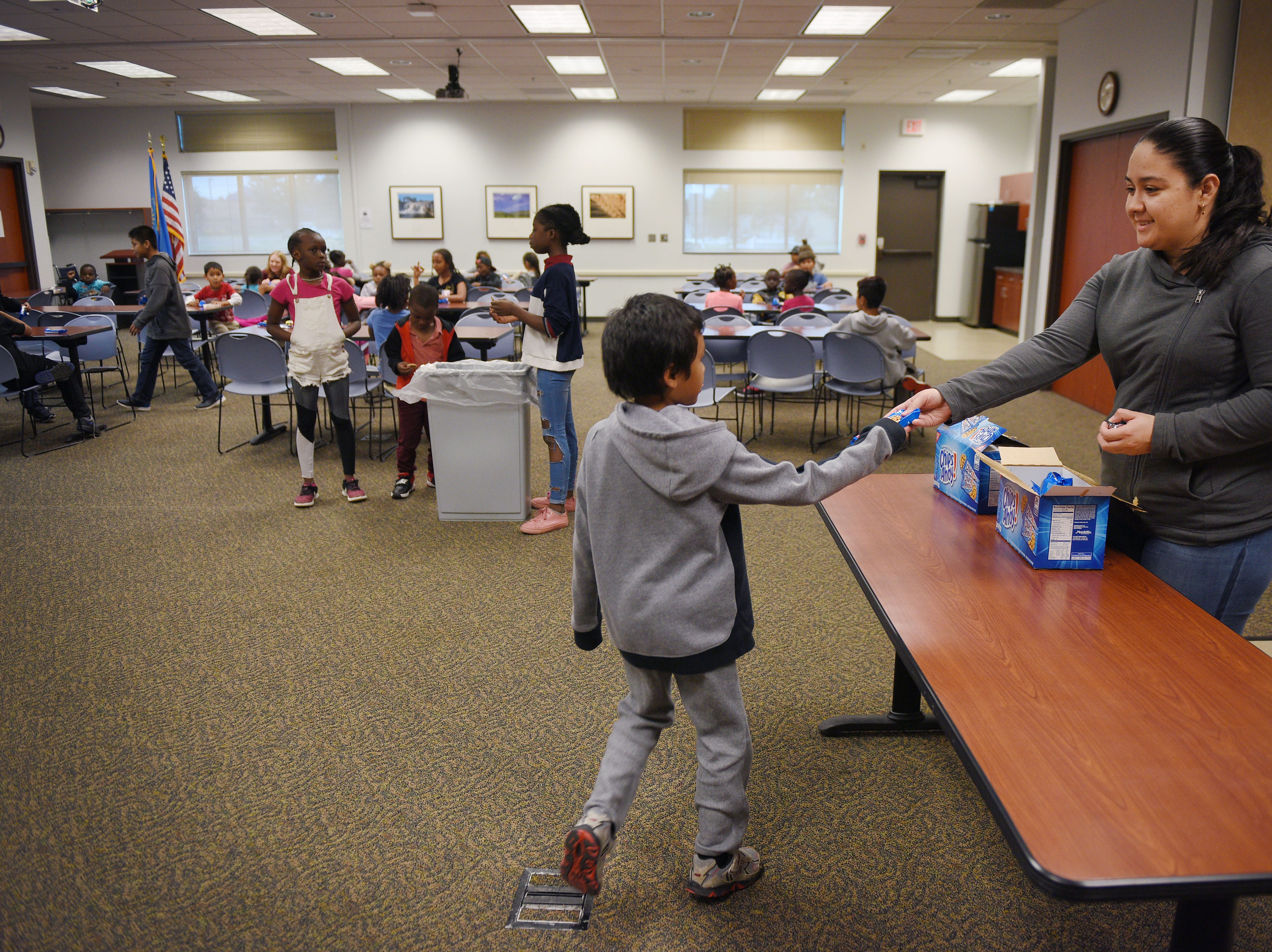 Monica Melendez hands out snacks to kids at the Oak View Library after school Wednesday, Sept 26, at the library in Sioux Falls. The after school snacks are provided by Feeding South Dakota.