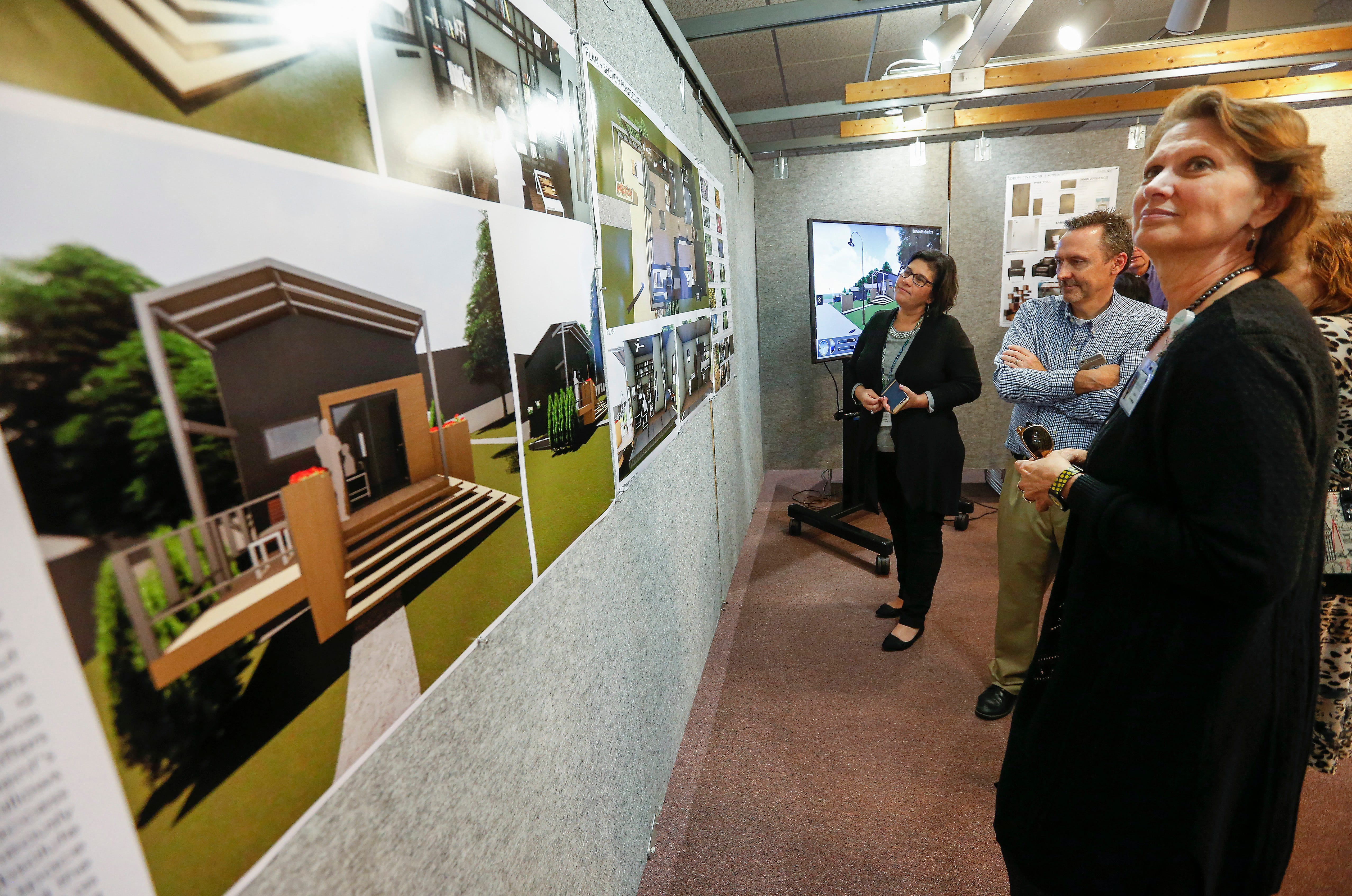 People look at renderings of a tiny house that was designed by architecture students at Drury University and will be the final house at Eden Village.