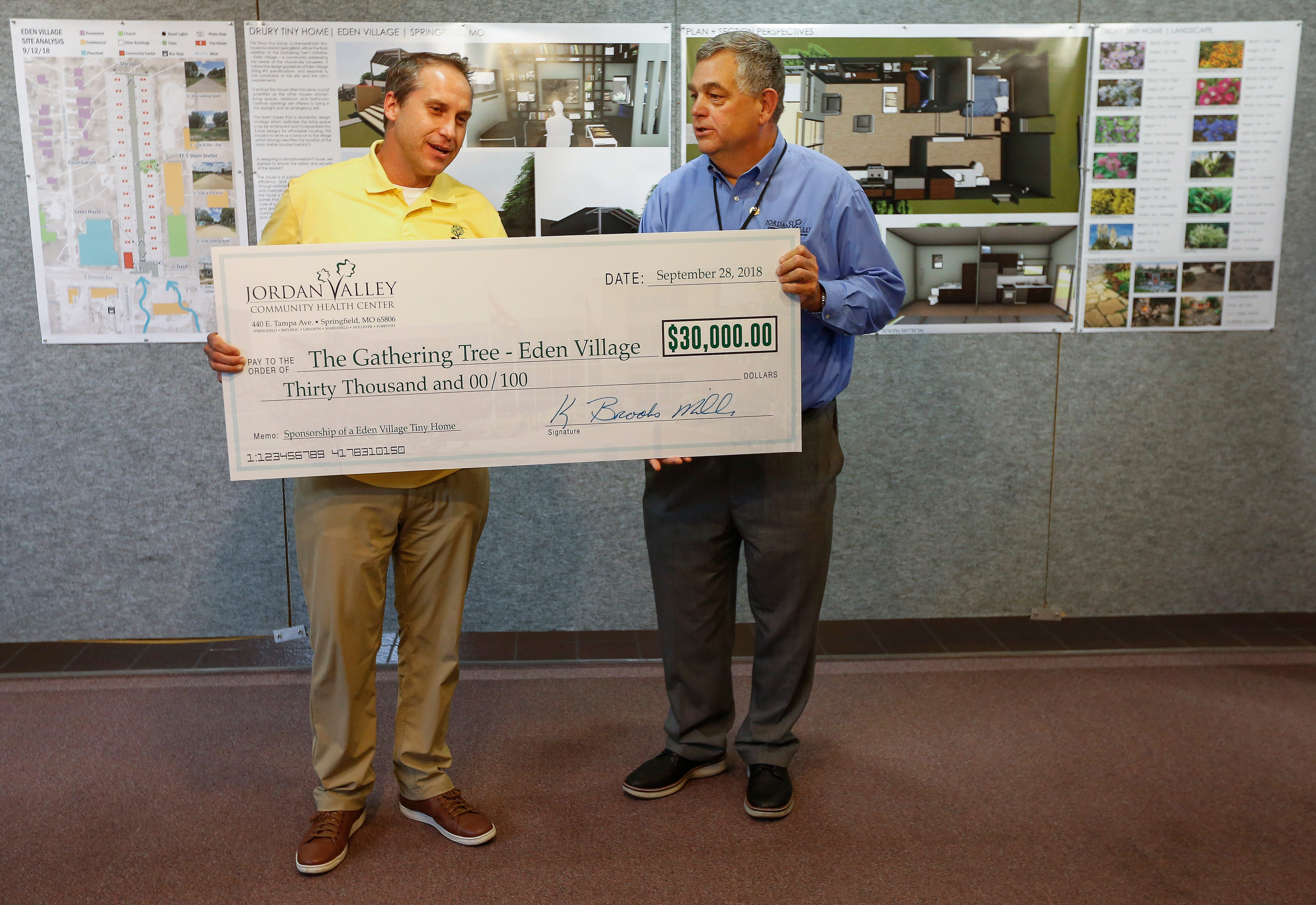 Nate Schlueter, left, the COO of Eden Village, accepts a check presented to him by K. Brooks Miller, President and CEO of Jordan Valley Community Health Center, that will help pay for the final tiny house in Eden Village.