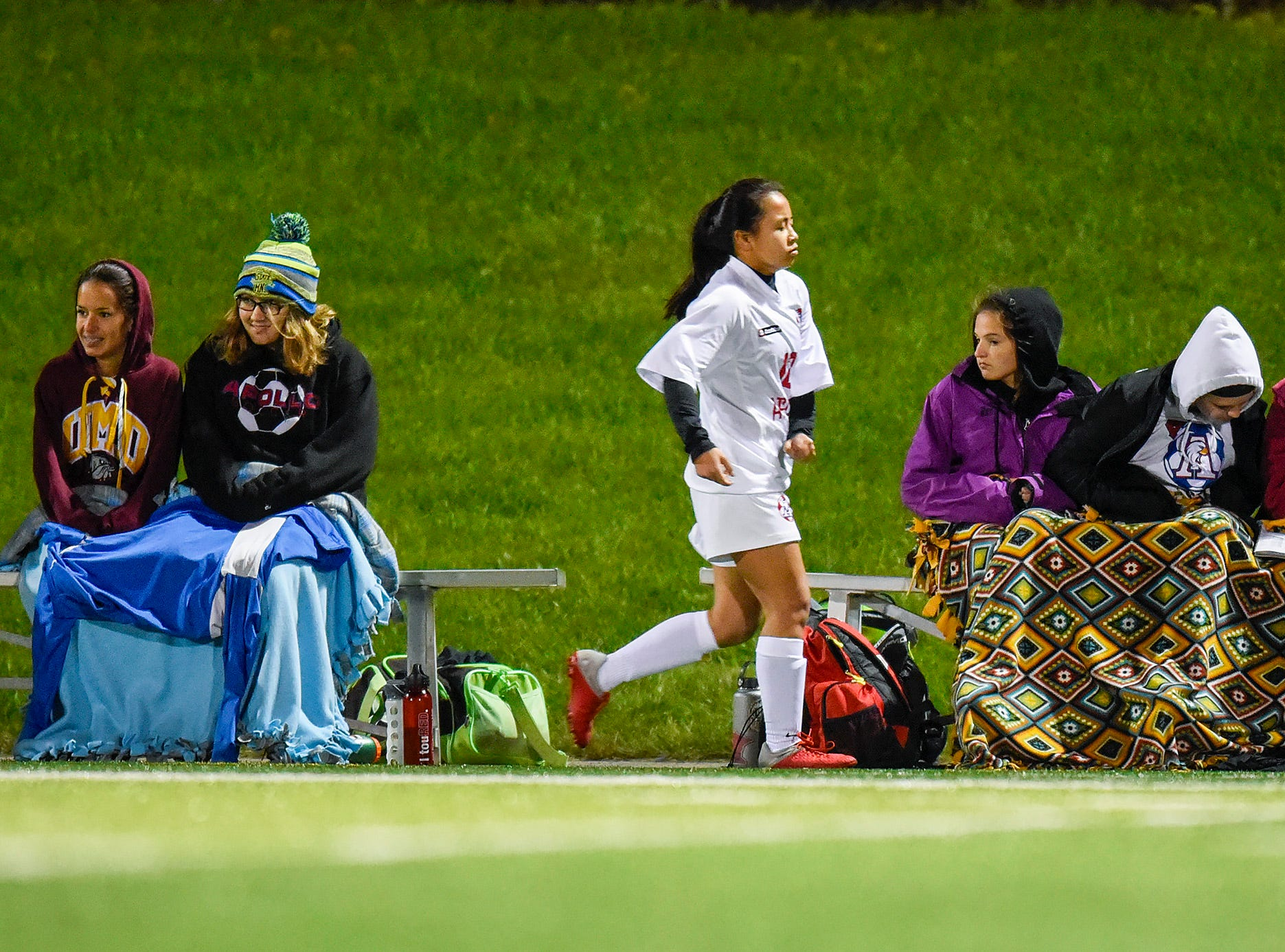 Apollo players stay warm on the bench during the second half Thursday, Sept. 27, at Husky Stadium.
