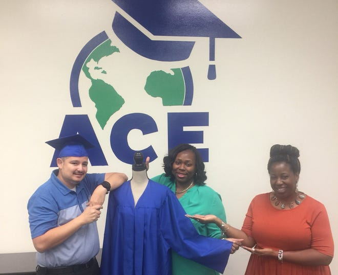 Taita Scott, principal of Riley Elementary School and Regina Browning, principal of Adult & Community Education School announce the schools' partnership that will provide GED® classes at Riley beginning Oct. 1. Randall Austin, assistant principal of Riley dons a mortarboard as a reminder to his students' parents the classes will help them reach a goal many of them have: to earn a high school diploma.