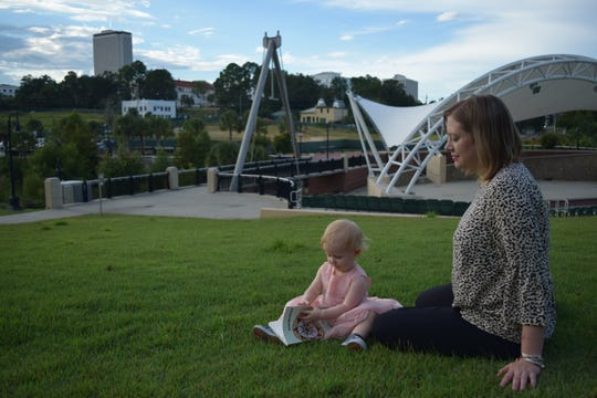"""Erin Hoover, who teaches at Florida State University, spends time with daughter, Hester, holding her """"Barnburner"""" poetry book at Cascades Park."""
