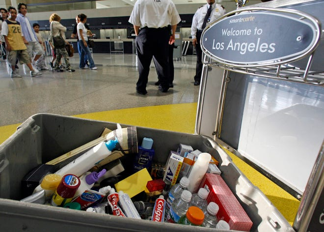 In this file photo, Transportation Security Administration personnel watch as travelers make their way past a container of banned carry-on items at Los Angeles International Airport.