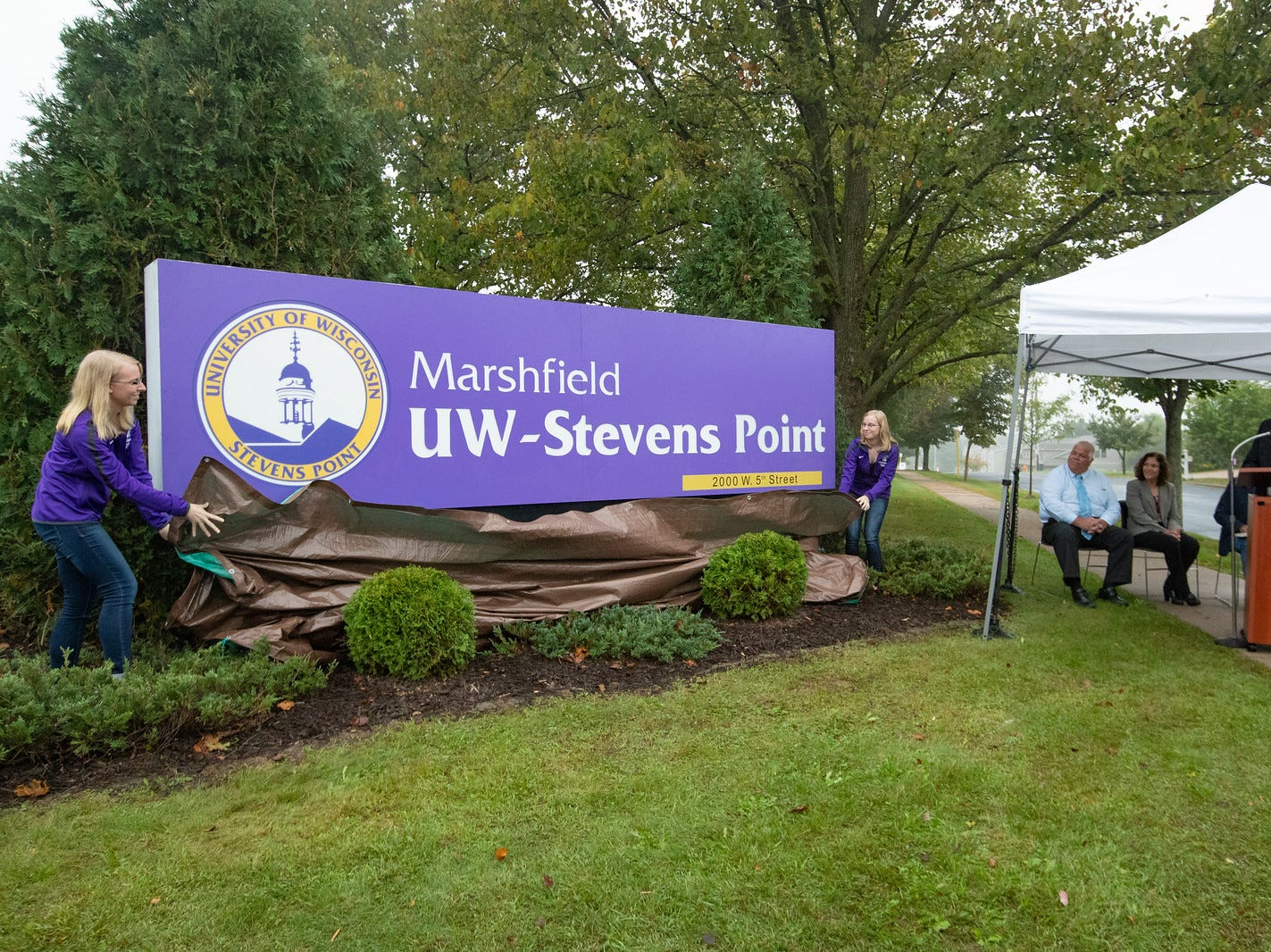 UW-Stevens Point at Marshfield students Tiffany Guden, left, and Tara Guden unveil a new campus sign Sept. 19 along West Fifth Street in Marshfield on the former UW-Marshfield/Wood County campus.