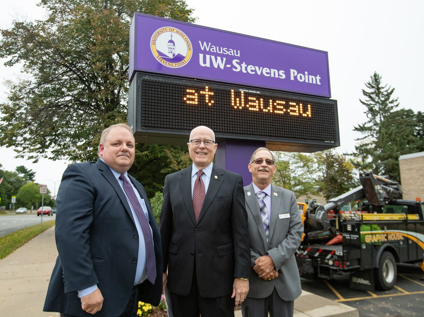 UW-Stevens Point Chancellor Bernie Patterson, Wausau Mayor Robert Mielke and Marathon County Board Chairman Kurt Gibbs pose with the new UW-Stevens Point at Wausau sign.