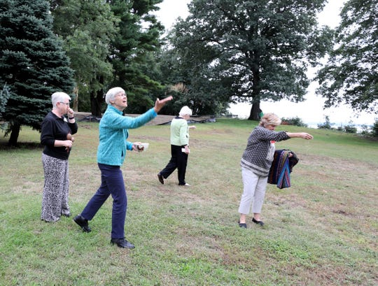Sister Bette Ann Jaster with the Dominican Sisters of Hope tosses seeds blessed with prayers Friday at the Mariandale Center property in Ossining.  A ceremony for a land conservation easement that will protect 34 acres of open space was held at the center.