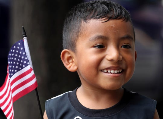 Mateo Barrios, 4, of Port Chester holds his American flag while walking along Westchester Ave. with his mother and brother Aug. 11, 2018.