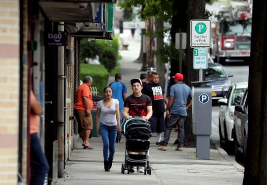 People walk along Westchester Ave. in Port Chester Aug. 11, 2018.