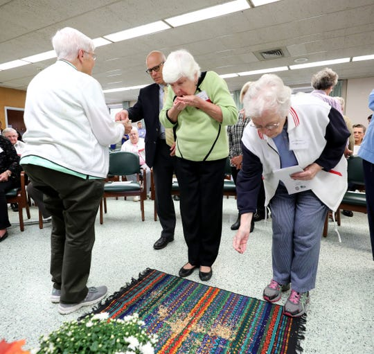Nuns and other guests blow prayers into seeds and place them on a cloth Friday at the Mariandale Center property in Ossining.  A ceremony for a land conservation easement that will protect 34 acres of open space was held at the center.
