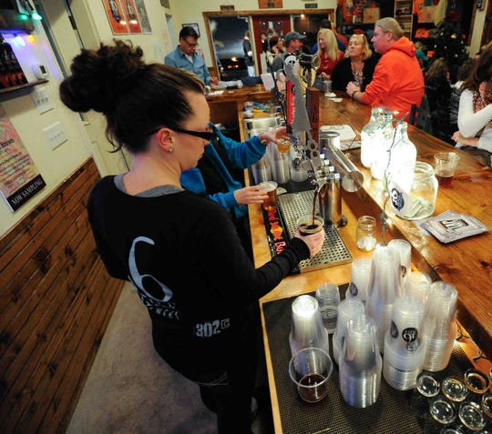 16 Mile bartender Heather Snyder pours a glass of Delaware Oyster Stout  in 2014.