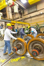 Machinists work on a wheel set at the Wilmington Shops.