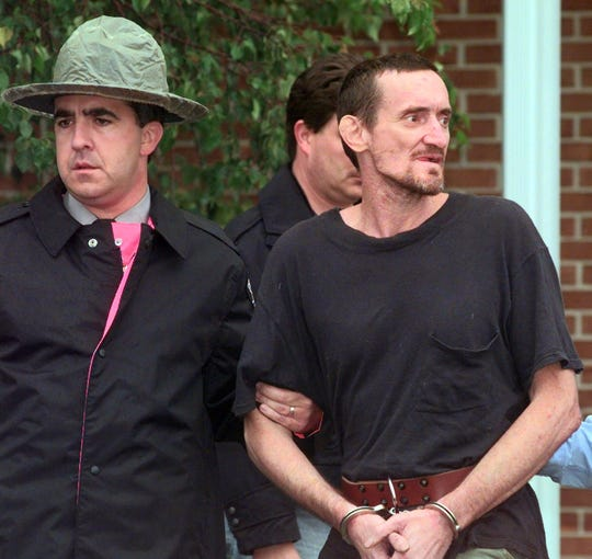 Escaped murderer Norman Johnston is escorted from the Avondale, Pa., state police barracks by after he was recaptured early Friday, Aug. 20, 1999. Johnston had been on the run for nearly three weeks since escaping from the state prison at Huntingdon, Pa. Johnston was serving a life sentence for murder.