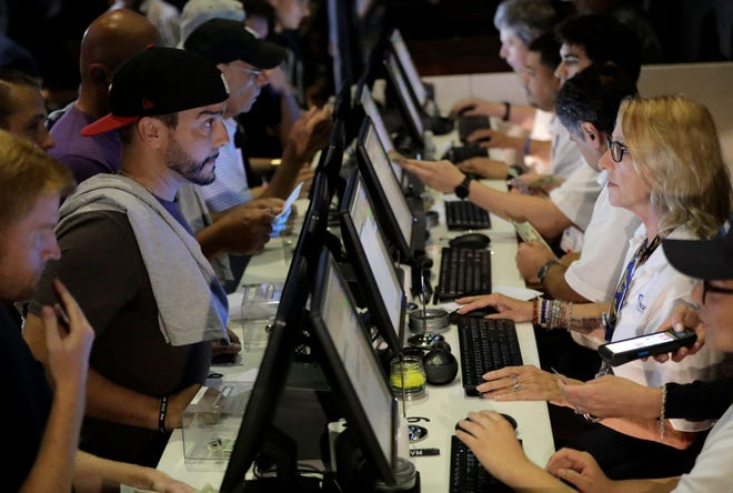 In this July 14, 2018, file photo, people, left, talk to tellers while placing bets at the Meadowlands Racetrack, in East Rutherford, N.J. House Republicans say they are strongly in favor of new federal regulations on sports gambling after the Supreme Court allowed states to start opening sports books.