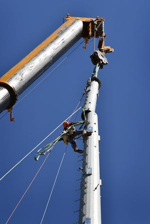 Tony Mayle of MUTI tower construction prepares to align the top section of a 160-foot tall cellphone tower Friday afternoon in the 1200 block of Broad Street.