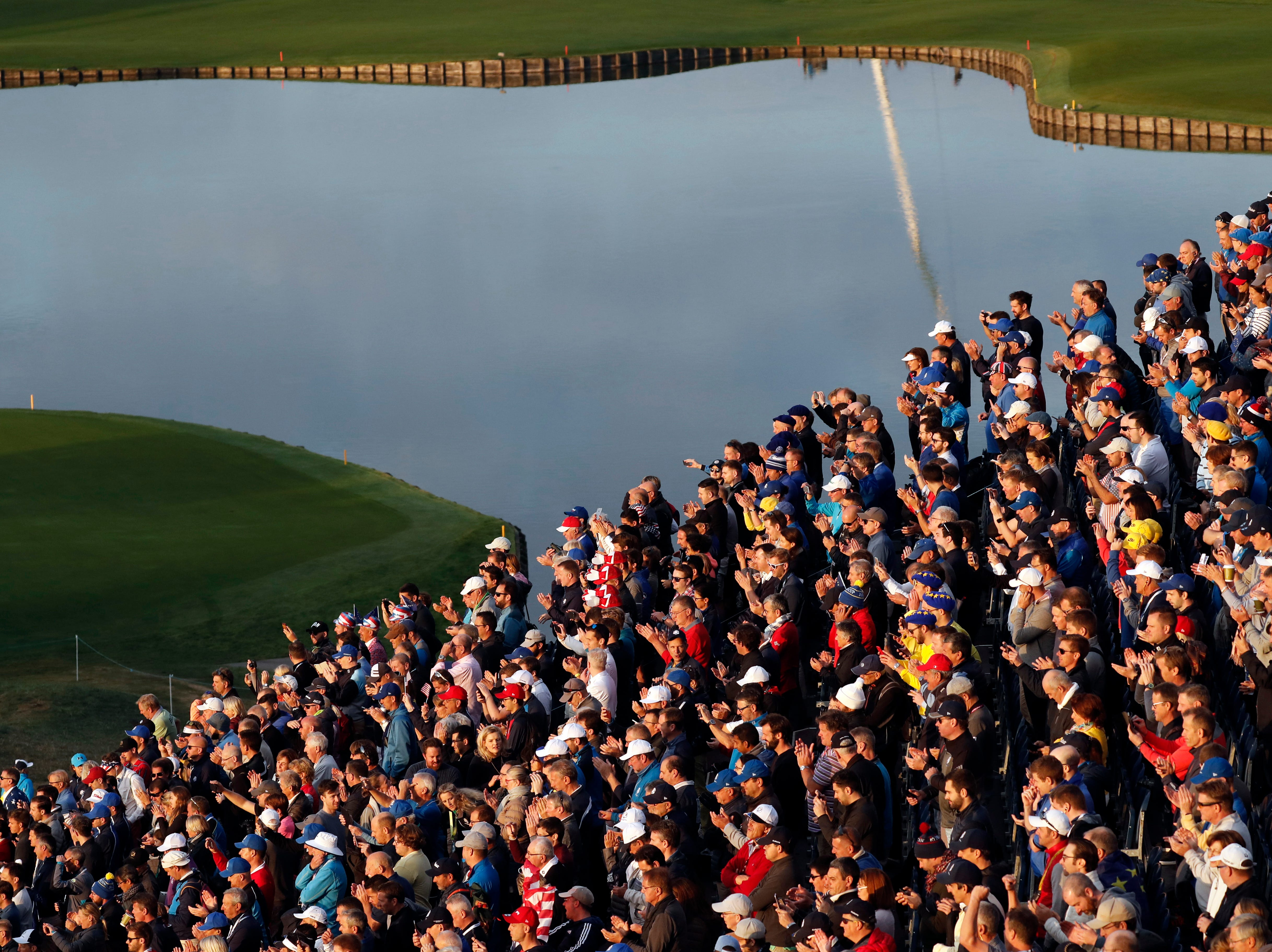 Supporters watches players while standing in a grandstand overlooking the first tee.
