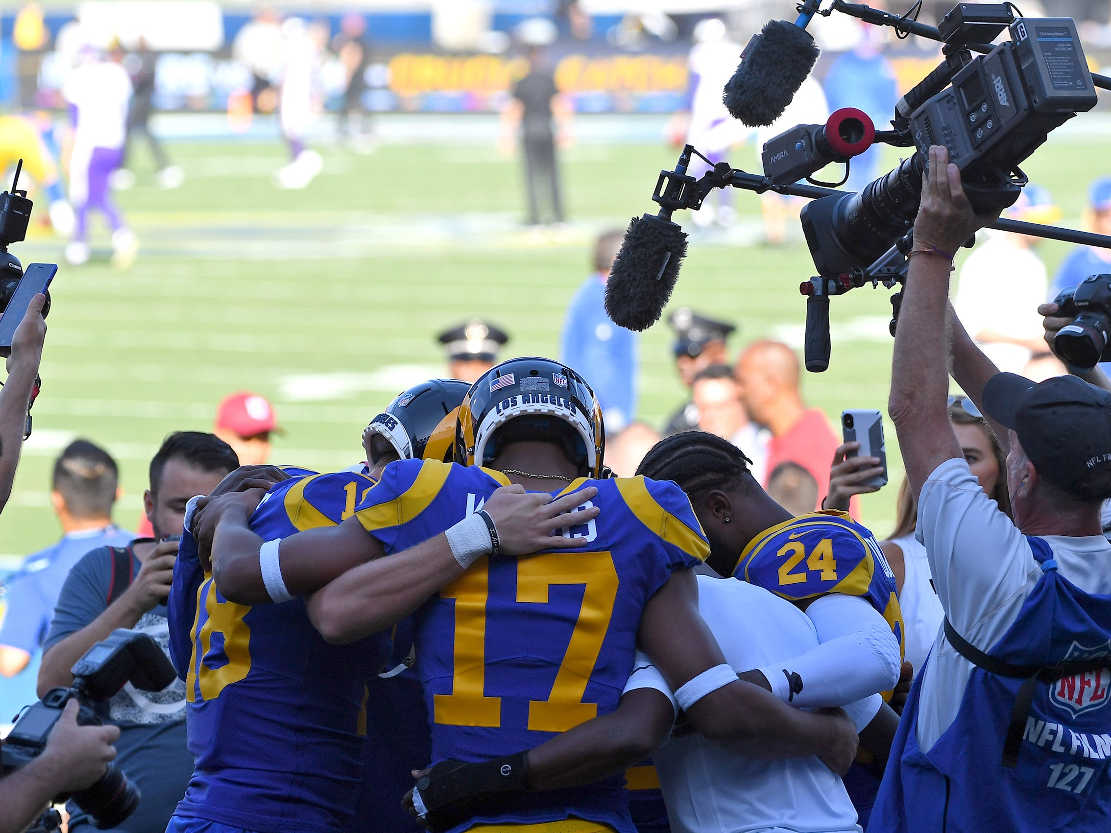 The Los Angeles Rams' Robert Woods (17), Cooper Kupp (left) and Blake Countess (24) huddle before they take the field to warm up before the game at the Los Angeles Memorial Coliseum.