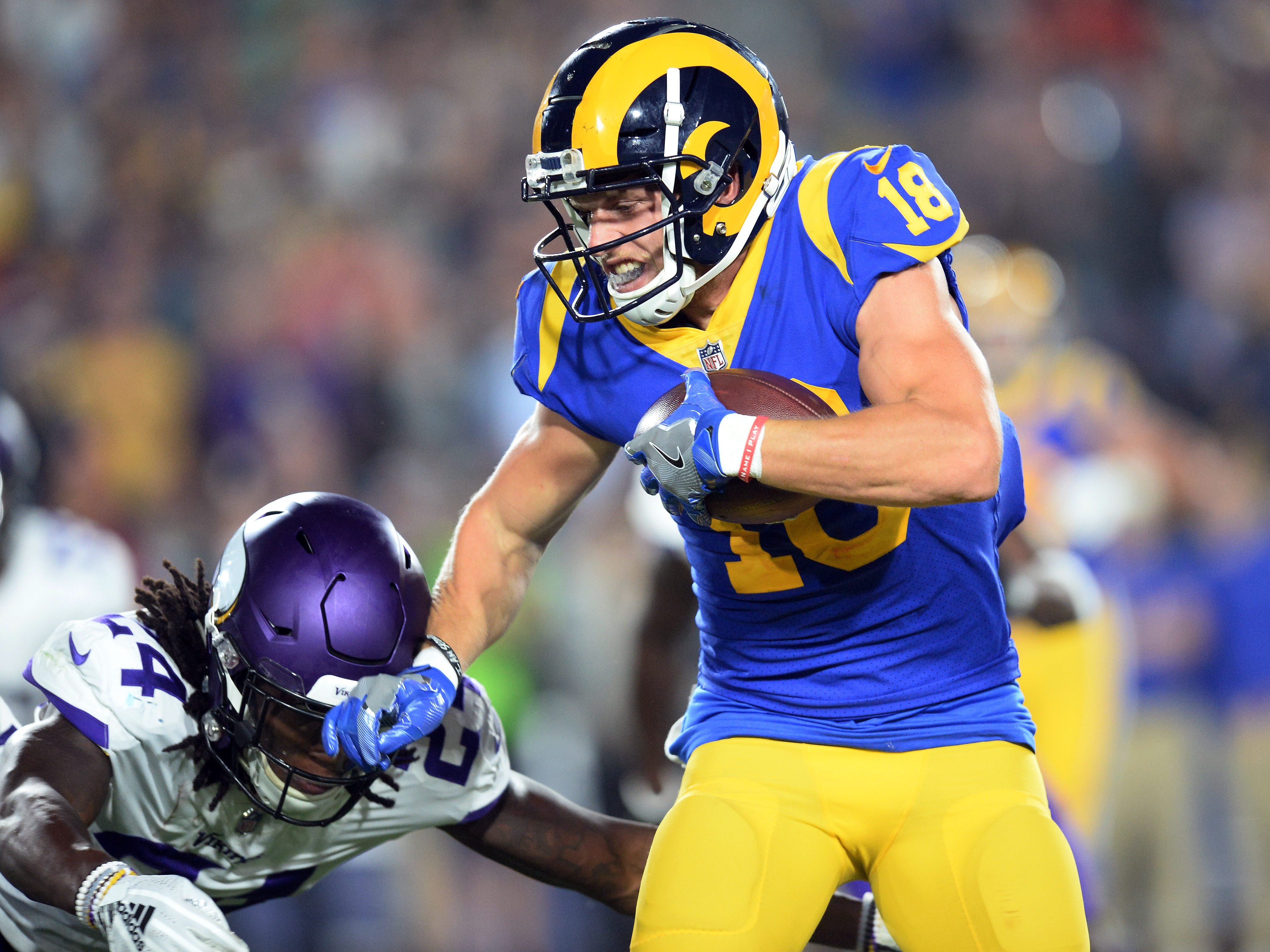 Los Angeles Rams wide receiver Cooper Kupp runs the ball against the Vikings defense.