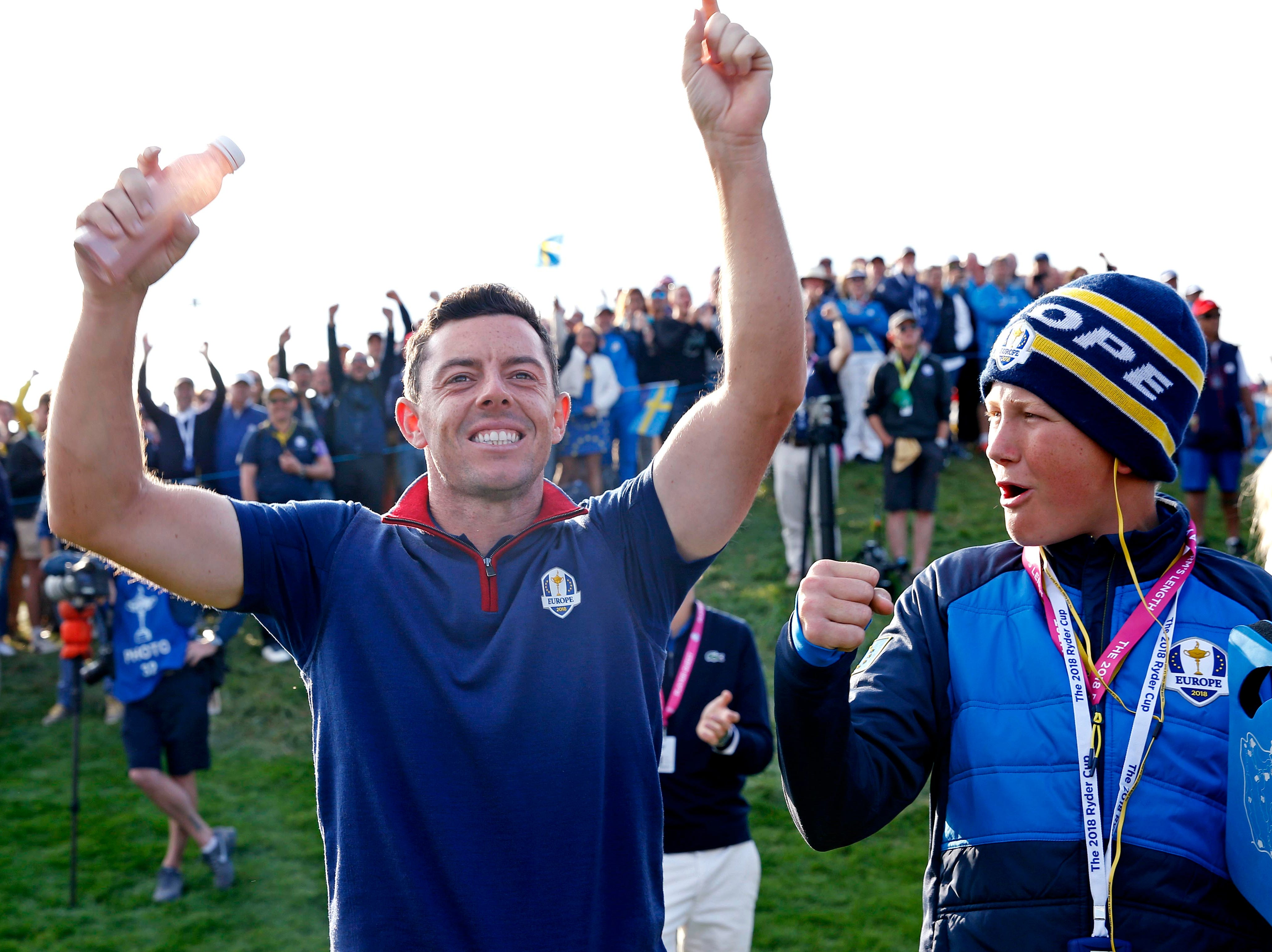 Europe's Rory McIlroy reacts with Ian Poulter's son Luke Poulter on the 16th green during the Ryder Cup Friday afternoon matches.