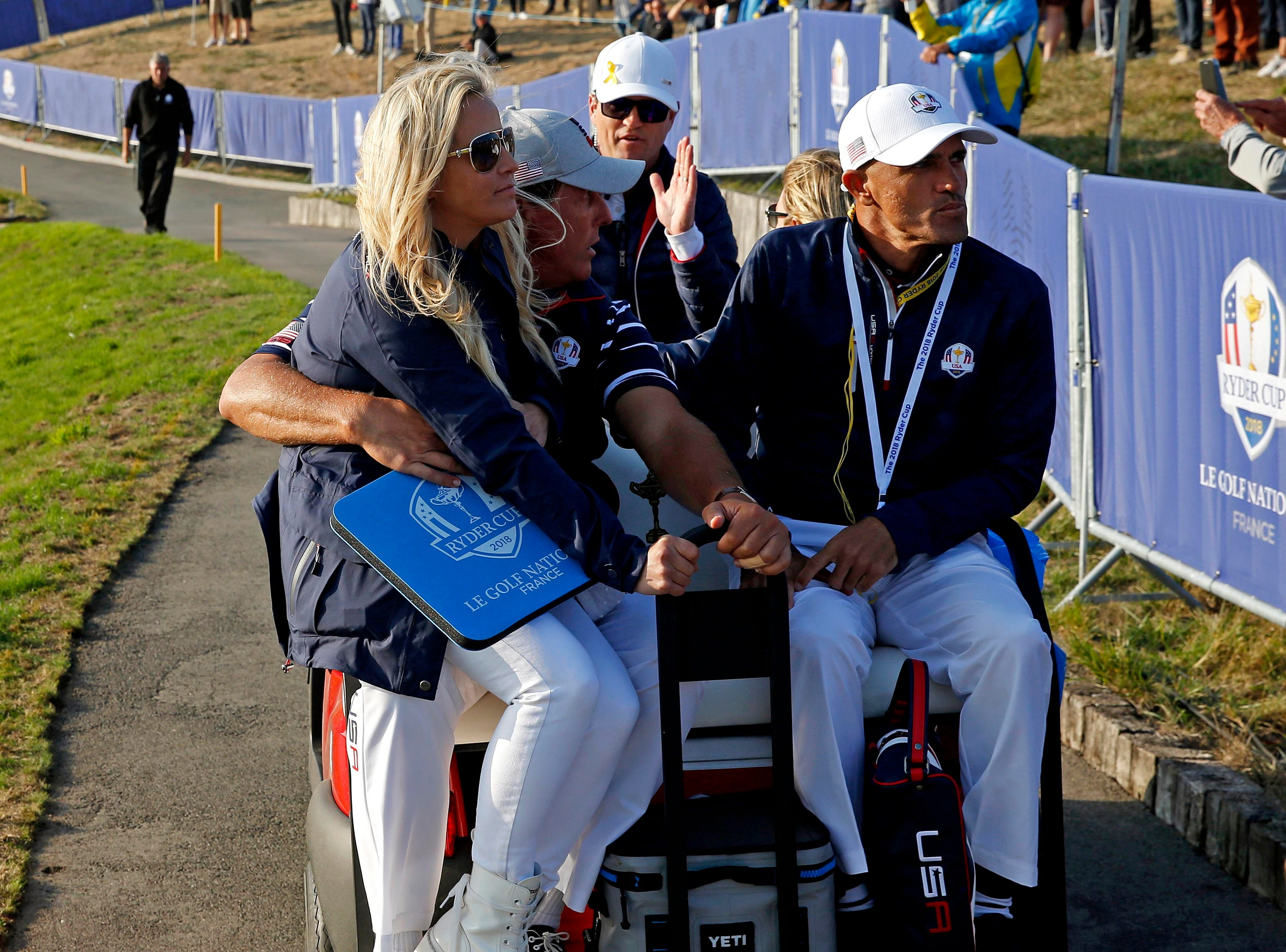 Phil Mickelson and his wife Amy Mickelson ride back to the clubhouse during the Ryder Cup Friday afternoon matches.