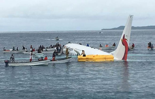 Local fishing boats move in to recover the passengers and crew of Air Niugini flight following the plane crashing into the sea on its approach to Chuuk International Airport in the Federated States of Micronesia.