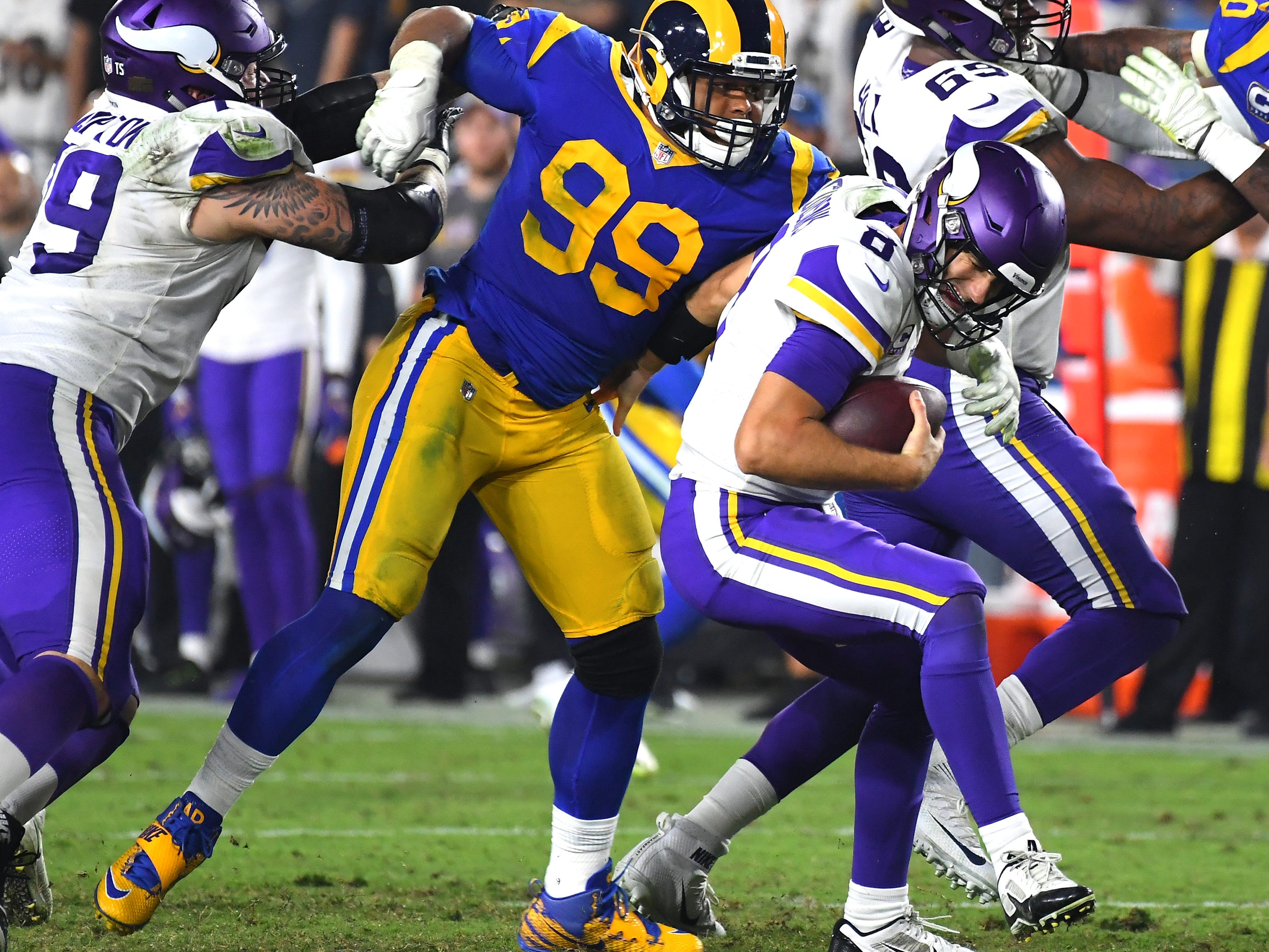 Minnesota Vikings quarterback Kirk Cousins scrambles in the pocket and avoids a sack by Los Angeles Rams defensive tackle Aaron Donald.
