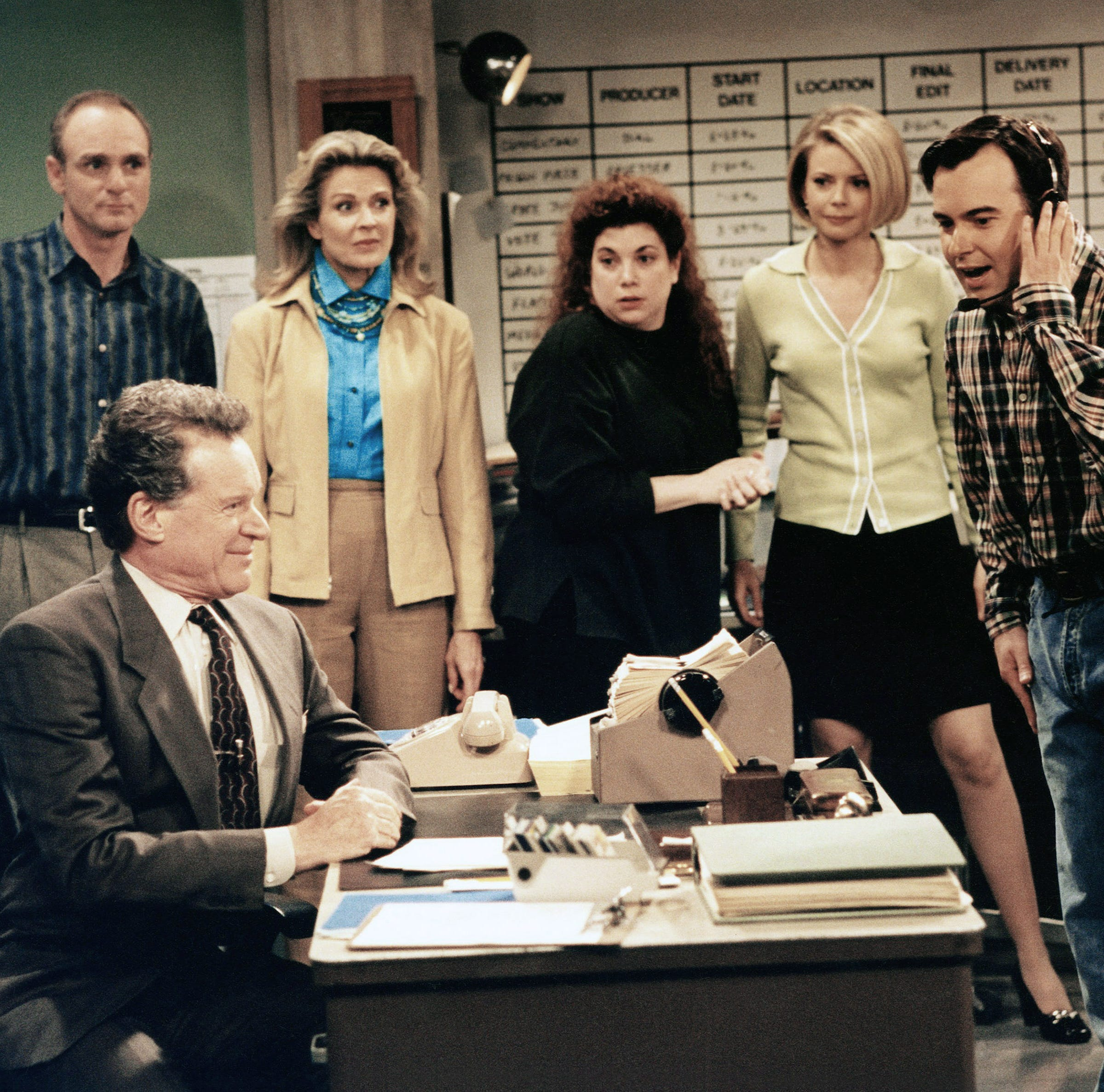 Cast photo of the Murphy Brown cast from 1998. Note the landline phone, rolodex and floppy disks.