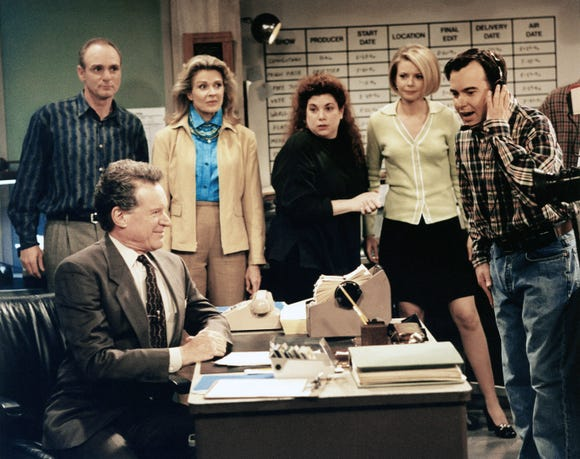 Cast photo of the Murphy Brown cast from 1988. Note the landline phone, rolodex and floppy disks.