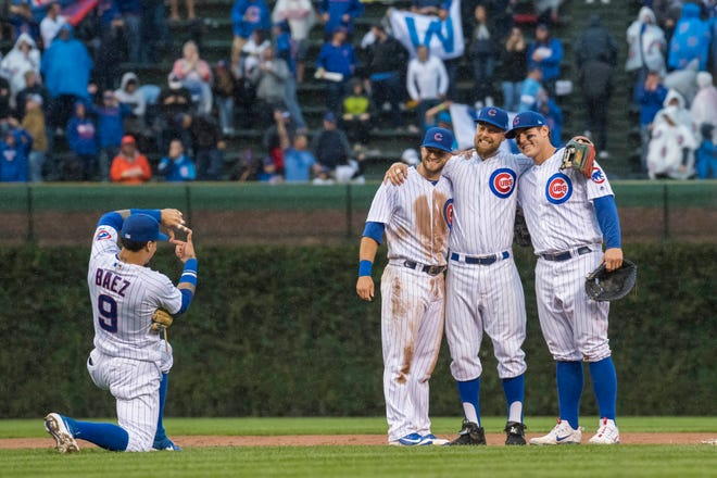 Javier Baez frames David Bote (left), Ben Zobrist (center) and Anthony Rizzo (right) after the Cubs victory over the  Cardinals.