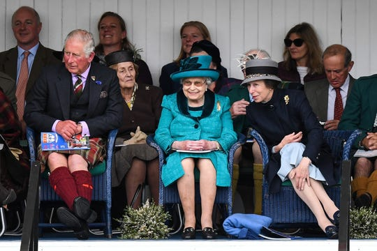 : Queen Elizabeth II, flanked by son Prince Charles and daughter Princess Anne, attend one of their favorite events, the annual Braemar Highland Gathering Highland Games on September 1, 2018 in Braemar, Scotland.