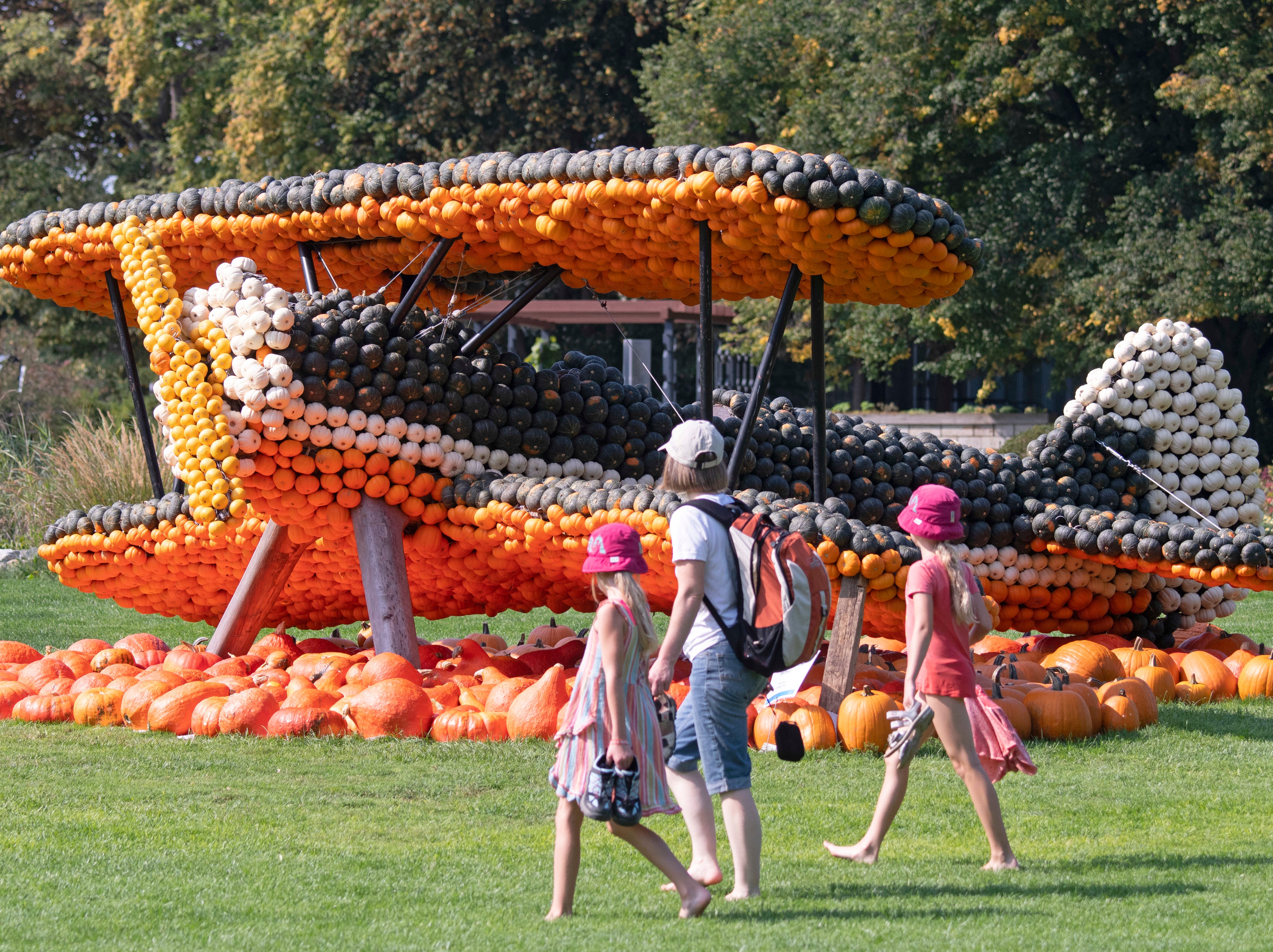 Visitors walk in front of a sculpture displaying an airplane during the autumn exhibition a horticultural exhibition in Erfurt, Germany on Sept. 5, 2018. Gardeners created different sculptures with thousands of pumpkins.