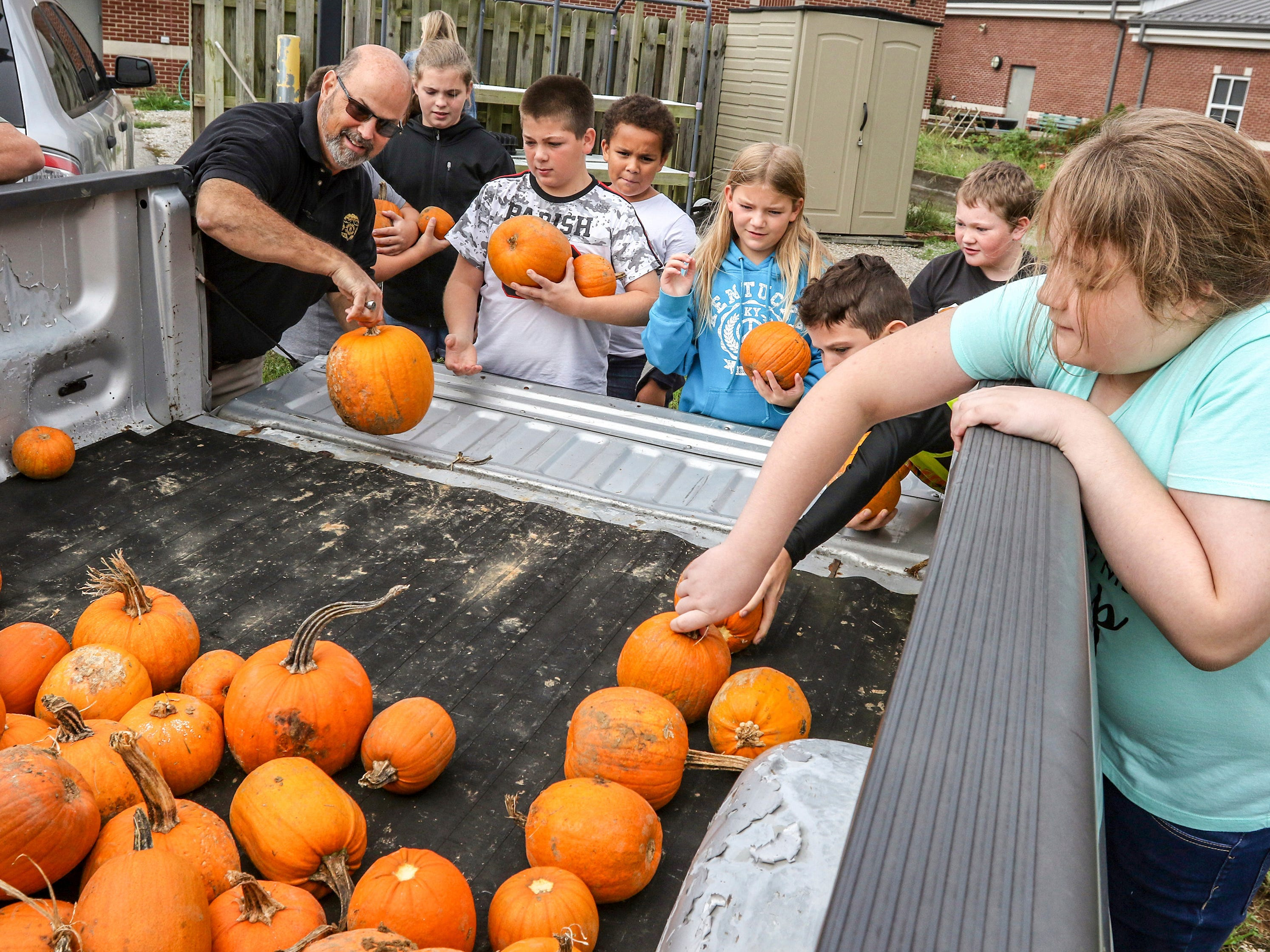 Sgt. Keith Stiff with the Daviess County Detention Center, left, helps West Louisville Elementary School fifth grade students, from left, Adaya Humphrey, William Hoggard, Trevan Coiles, Alyssa Vowels, Corban Waltrip, Robert Davis and Miley Gamblin unload 100 pumpkins from the back of a pickup truck on Sept. 26, 2018, in Owensboro, Ky. The pumpkins, donated by the jail and grown by inmates, will be available for painting during the school's Fall Festival.