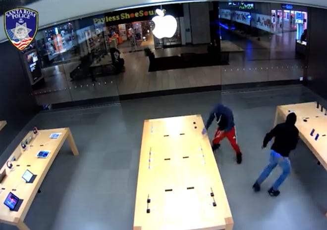 A screen grab of security footage showing robbers enter an Apple store in Santa Rosa, Calif., and steal multiple Apple devices.