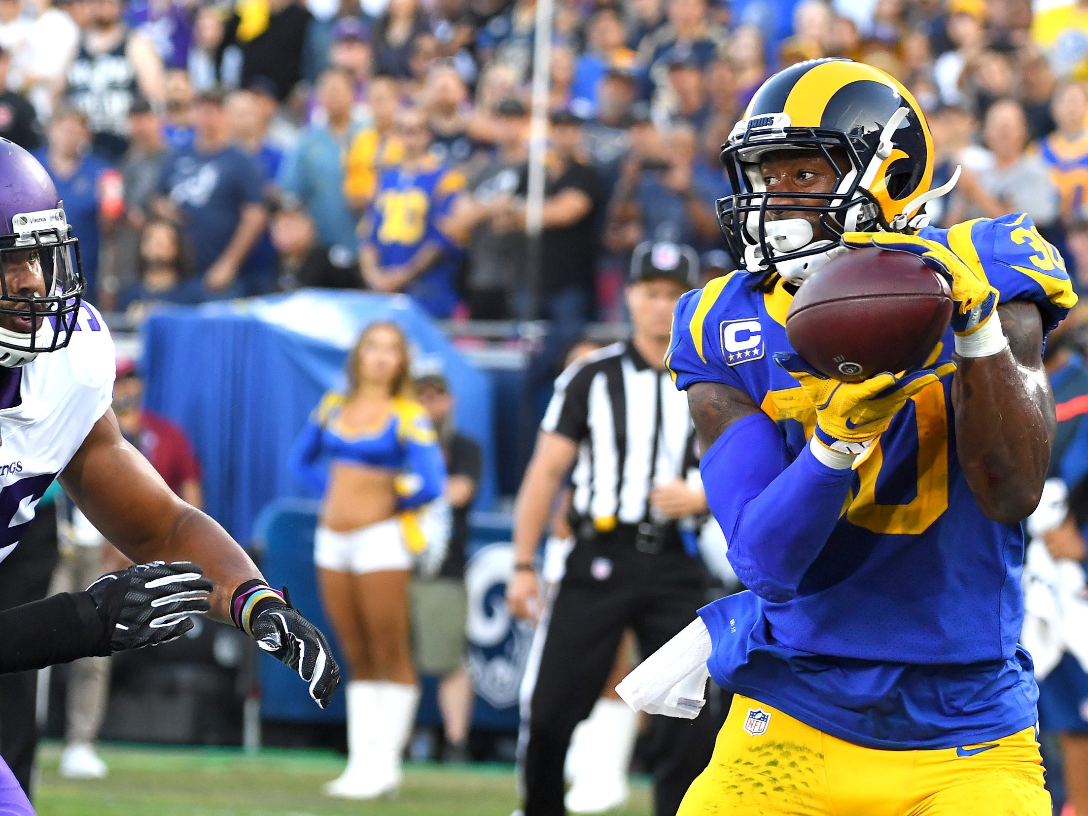 Los Angeles Rams running back Todd Gurley catches the ball in front of Minnesota Vikings linebacker Anthony Barr (55) to score a touchdown in the first quarter of the game at the Los Angeles Memorial Coliseum.