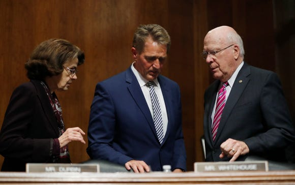 Sen. Jeff Flake, R-Ariz., center, talks to Sen. Dianne Feinstein, D-Calif, left, and Sen. Patrick Leahy, D-Vt., during a delay in the Senate Judiciary Committee hearing, Friday, Aug. 28, 2018 on Capitol Hill in Washington.  (AP Photo/Pablo Martinez Monsivais) ORG XMIT: DCPM202