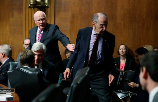 Sen. Patrick Leahy, D-Vt., reaches toward Senate Judiciary Committee Chairman Chuck Grassley, R-Iowa during a delay in the committee vote before the Senate Judiciary Committee on Capitol Hill in Washington, Friday, Sept. 28, 2018. (AP Photo/Andrew Harnik, Pool) ORG XMIT: WX201