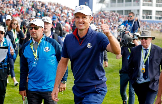 European golfer Justin Rose reacts to making a putt on the 14th hole during the morning Fourballs Session at Le Golf National.