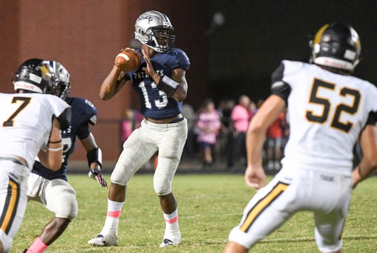 Powdersville senior Tay Cureton passes near Crescent junior Jayden Vincent during the first quarter at Powdersville High School on Friday, September 28, 2018.