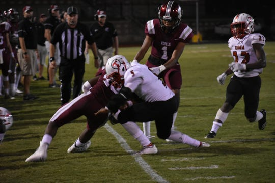 Tioga senior defensive back De'monde Mitchell (5) tackles Pineville's Bruce Jackson (46) out of bounds during the Indians' 48-35 loss at Pineville Friday night.