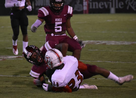 Pineville cornerback D.J. Conston (12) tackles Tioga receiver Deven Franklin (23) during the Rebels' 48-35 win Friday night. Franklin led the Indians with nine catches for 107 yards and a touchdown.