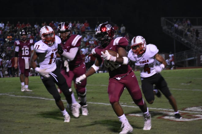 Pineville freshman running back Bruce Jackson (46) is chased by Tioga defenders Ty'darian Quinney (4) and Trey Cherry (17) during the Rebels' 48-35 win Friday night.