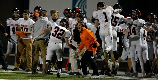West De Pere players and coaches celebrate a fumble recovery against Menasha in a Bay Conference football game Friday at Calder Stadium in Menasha.