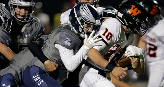 Menasha defenders try to tackle Josh Blount of West De Pere in a Bay Conference football game Friday, September 28, 2018, at Calder Stadium in Menasha, Wis.Ron Page/USA TODAY NETWORK-Wisconsin