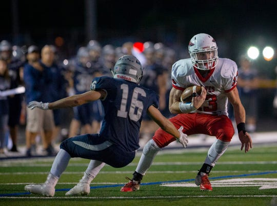 Manalapana's Dale Sieczkowski makes a cut to avoid the outstretched arms of Howell's John Vuoso.  Manalapan Football vs Howell in Howell, NJ on September 28, 2018.